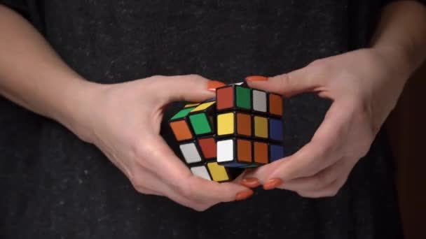 Female hands are trying to collect the colors of the rubiks cube. Puzzle games