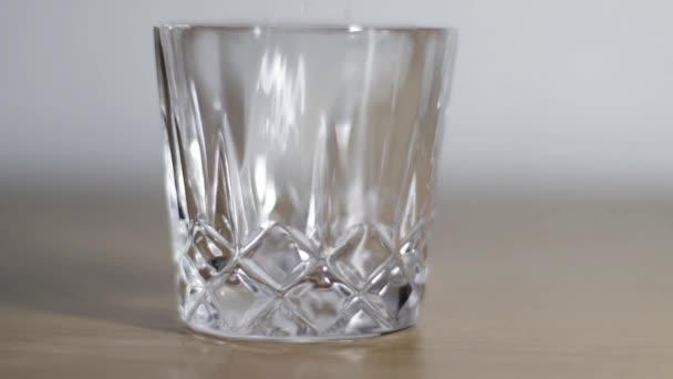 Ledové kostky padající do sklenice. Led ve sklenici. Prázdné křišťálové sklo.