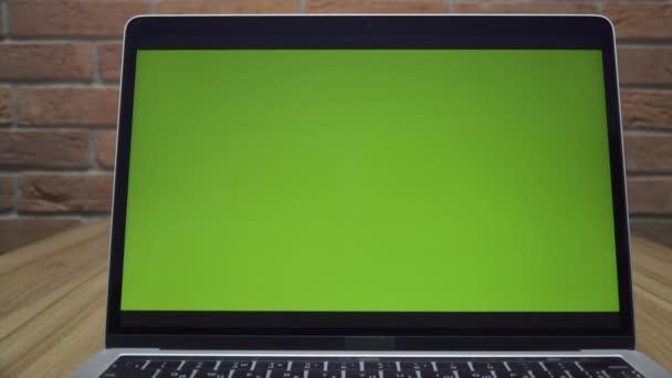 Laptop zöld képernyővel az irodában. Dolly zoom lövöldözés. Tetőtéri iroda. A háttérben egy téglafal..