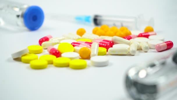 Colored tablets and pills,  medicine bottle and syringe on  white background. Medical preparations. 4k. Camera moves