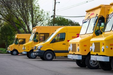 DHL truck fleet at a DHL service center facility. DHL International GmbH is an express delivery service, a division of the German logistics company Deutsche Post DHL- Sunnyvale, CA, USA - 2020