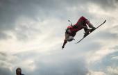 Junger Skifahrer springt in den Himmel