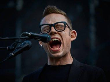 young man in eyeglasses singing in microphone