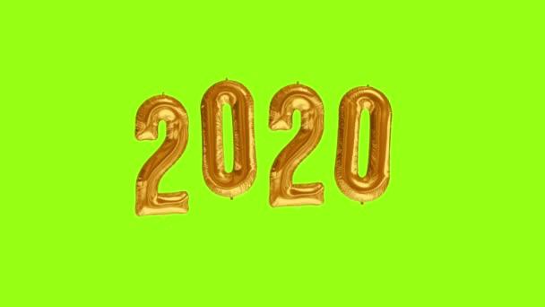 Nová oslava roku2020. Zlatá fólie balónky číslo 2020 na zeleném pozadí