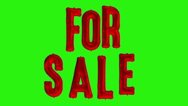 schwimmende Buchstaben zum Verkauf aus rotem Folienballon auf grünem Hintergrund