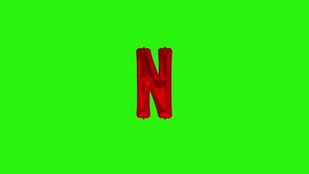Červené písmeno N. Červená fólie helium balón abeceda plovoucí na zelené obrazovce