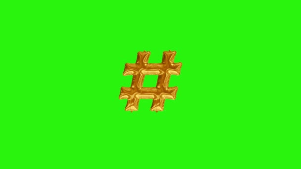 Golden symbol hash. Gold foil helium balloon symbol floating on green screen