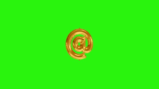 Golden symbol AT. Gold foil helium balloon symbol floating on green screen
