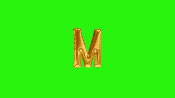 Zlaté písmeno M. Zlatá fólie helium balón abeceda plovoucí na zelené obrazovce