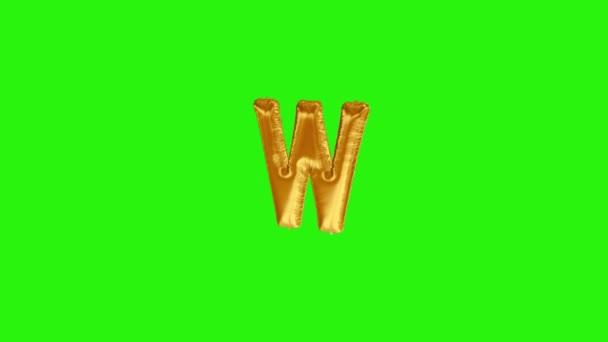 Golden letter W. Gold foil helium balloon alphabet floating on green screen