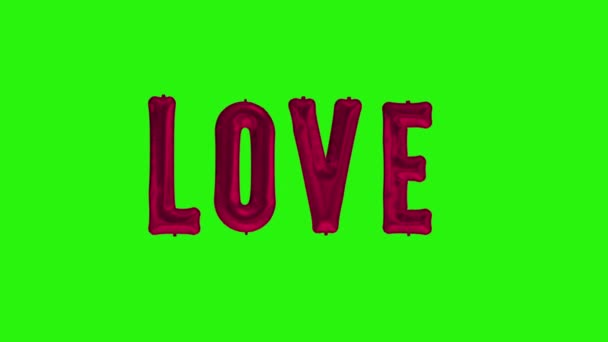 Word love from helium red foil balloon letters floating on green screen