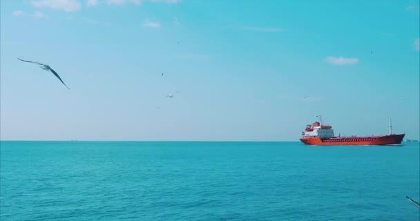 Nagy piros tartályhajó hajózik a kék tengeren a távolság a jobb oldalon nyáron