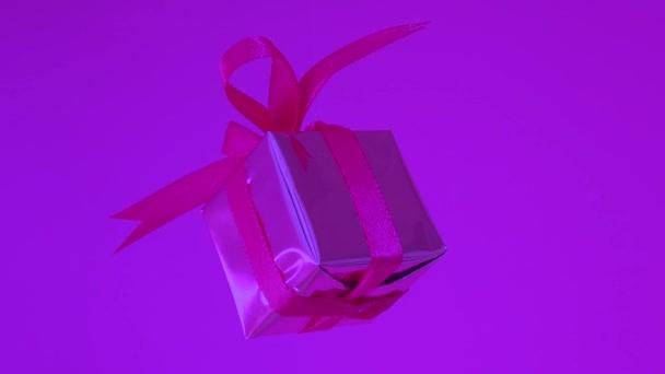 Geschenkkarton mit rotem Band, das sich auf neonviolettem Hintergrund dreht. 360-Grad-Rotation