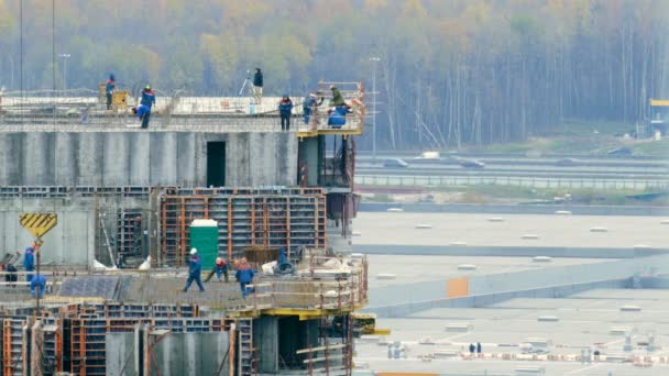 Construction workers mounting concrete formwork with crane during house building on the background of forest and road
