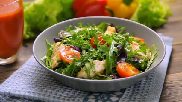 Fresh salad with chicken, tomatoes, arugula, mesclun, basil and tomato juice on a cloth napkin, on wooden table