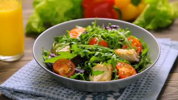 Fresh salad with chicken, tomatoes, arugula, mesclun, basil and orange juice on a cloth napkin, on wooden table