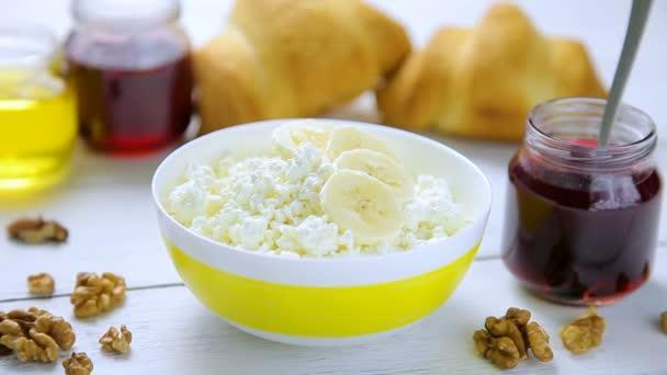 Zdravá snídaně - drobivé, tvaroh s banánem, vlašské ořechy, croissanty, medu a brusinkový džem v mísa stojící na dřevěný stůl