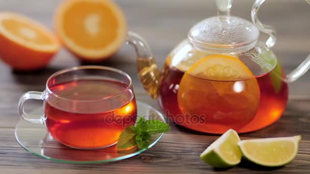 Glass teapot and cup of black tea with orange, lemon, lime and mint on a wooden table