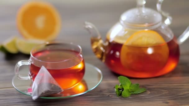 Glass teapot and cup with tea, next to which lies a bag of black tea with orange, lemon, lime and mint on wooden table
