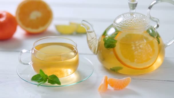Glass teapot and Cup with green tea, orange, Mandarin, lime and mint on white wooden table