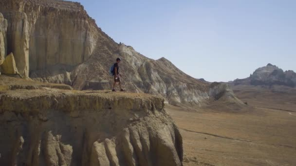 A young traveler stands on the edge of a cliff and drinks water