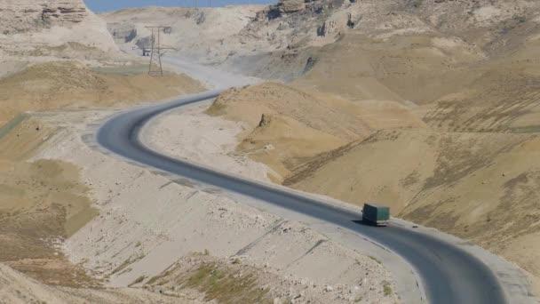 Ein LKW rast auf einer sonnigen Straße inmitten der Hügel langsam in die Rille