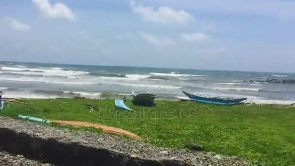 Tropická Pláž s čluny, ležící na písku. Pohled z projíždějícího vlaku. Srí Lanka