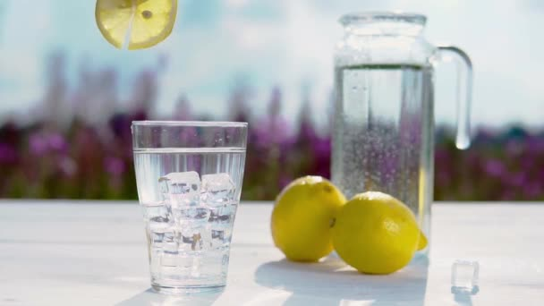 hand puts a slice of lemon on a glass of water and ice standing on a white table on the background of a decanter of water and two lemons. Beautiful still life of soft drinks