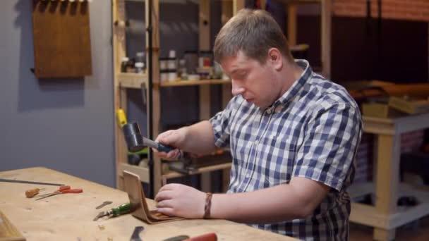 Meister der Herstellung handgefertigter Lederbrieftaschen schlägt einen Hammer auf das Werkzeug, das Löcher in das Leder macht. Obbler Arbeitsplatz