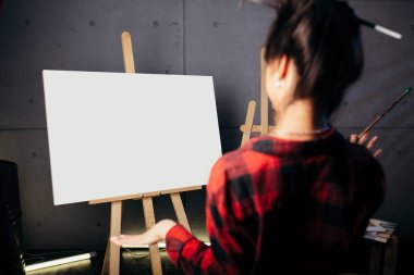 Blank Mock Up Canvas. Artist is in Studio in front of the easel and looks at the new abstract watercolor color painting.