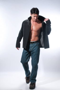 The sexy man is wearing jeans and a black jacket.