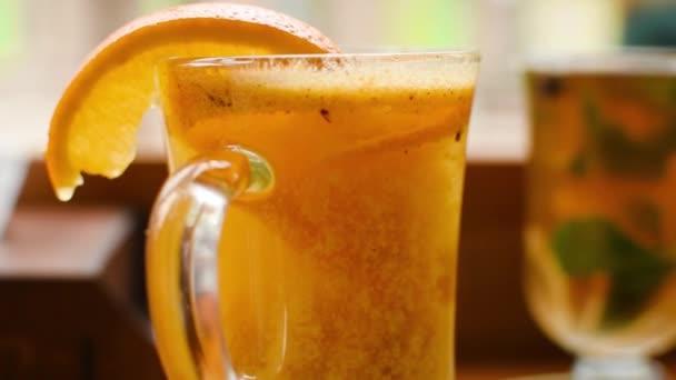 Weihnachts- und saisonales Getränkekonzept - Fruchtfleisch einer Orange bewegt sich im Glas, Nahaufnahme.