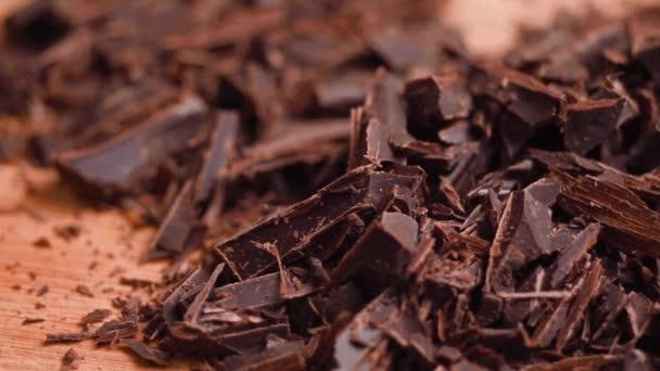 Nakrájená čokoláda detailní up na řeznou desku bočním pohybem