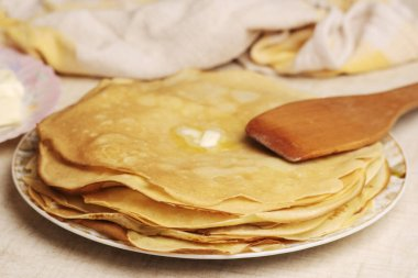 Pancakes on plate. Many pancakes are stacked. Thin pancakes with crispy crust. Maslenitsa. Pancakes for breakfast and carnival.