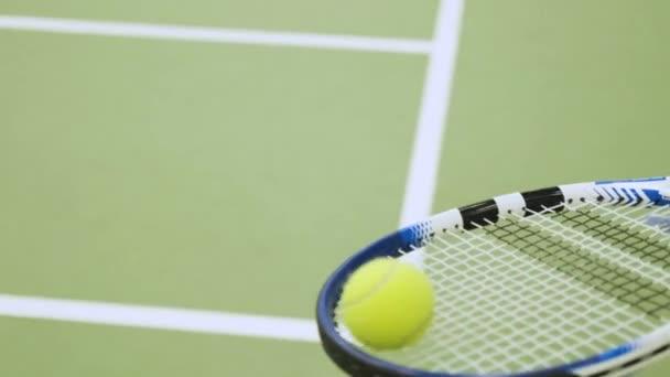 Tennis ball rolls and balances on racket