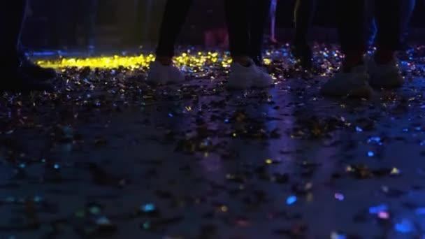 Holky tancují. Na podlaze jsou konfety..