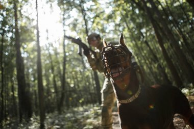 Picture of military man with dog and submachine gun
