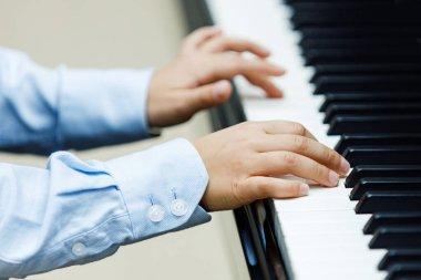 Small boy plays piano, close up