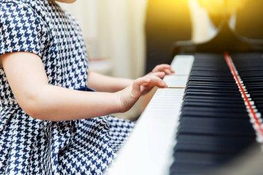 Girl playing piano, close up.