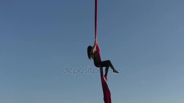 Woman climbs onto a hammock for a stunt.