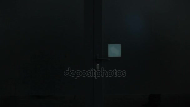 Räuber geht durch die Tür in der Nacht.
