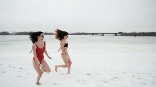 Ženy v plavkách řádit ve sněhu v blízkosti zamrzlé řeky