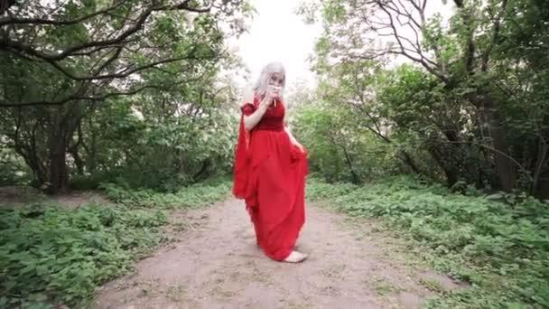 Egy piros ruhás nő whirls, a tánc, az erdő.