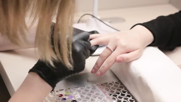 Die Maniküre-Meisterin zeichnet ein Muster auf die Nägel. Professionelle Maniküre im Salon.