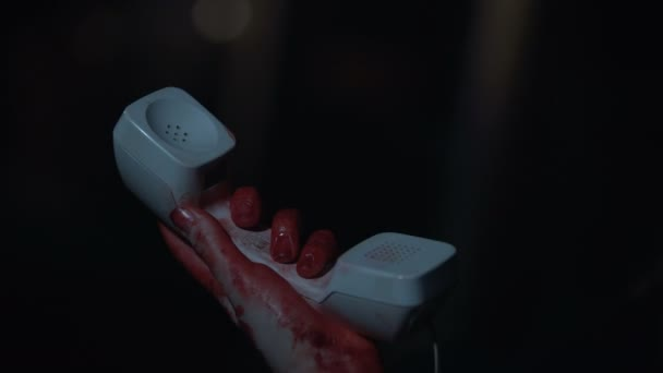 Victim with bloody hands finding telephone line cord disconnected, horror