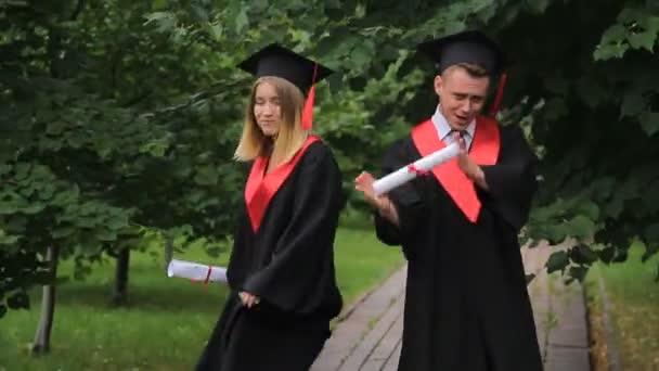 e29bb3de Szczęśliwy młodych absolwentów, taniec i z okazji ukończenia szkoły w  parku, w pobliżu Akademii