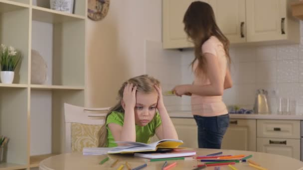 Overprotective mother controlling little daughter, making her read boring  book