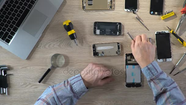 Man repairing broken gadget, diagnosing mobile phone problems, service  center