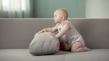 Funny Happy Baby Girl Jumping On Sofa Discovering World In Comfortable Diapers