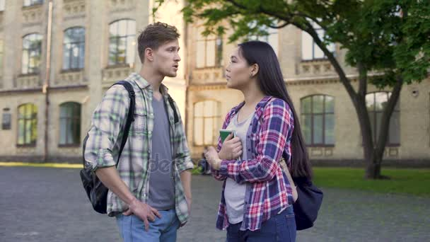 Male student talking with beautiful female friend
